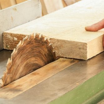 A close up of a woodworker's hand operating a piece of equipment